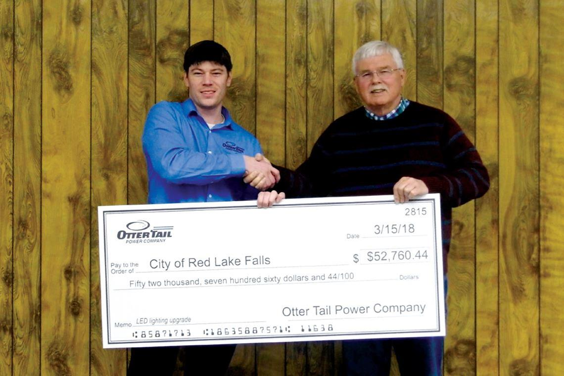 Allen Bertilrud accepts a rebate check from Roger Garton