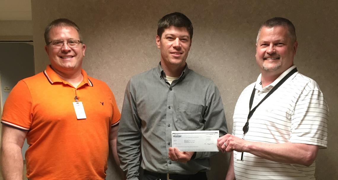 Rogert Garton presents a rebate check to Mahnomen Health Center staff
